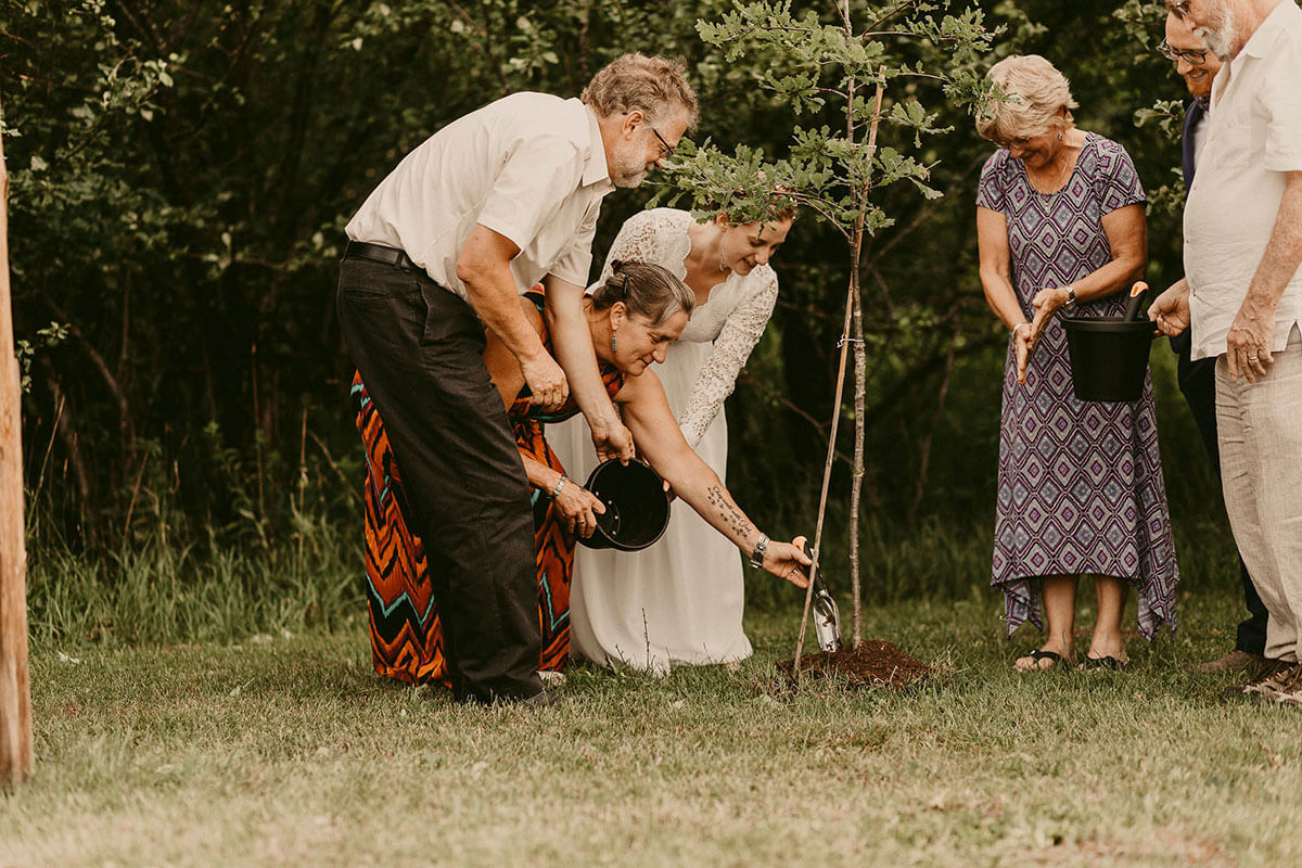 family planting tree during wedding ceremony
