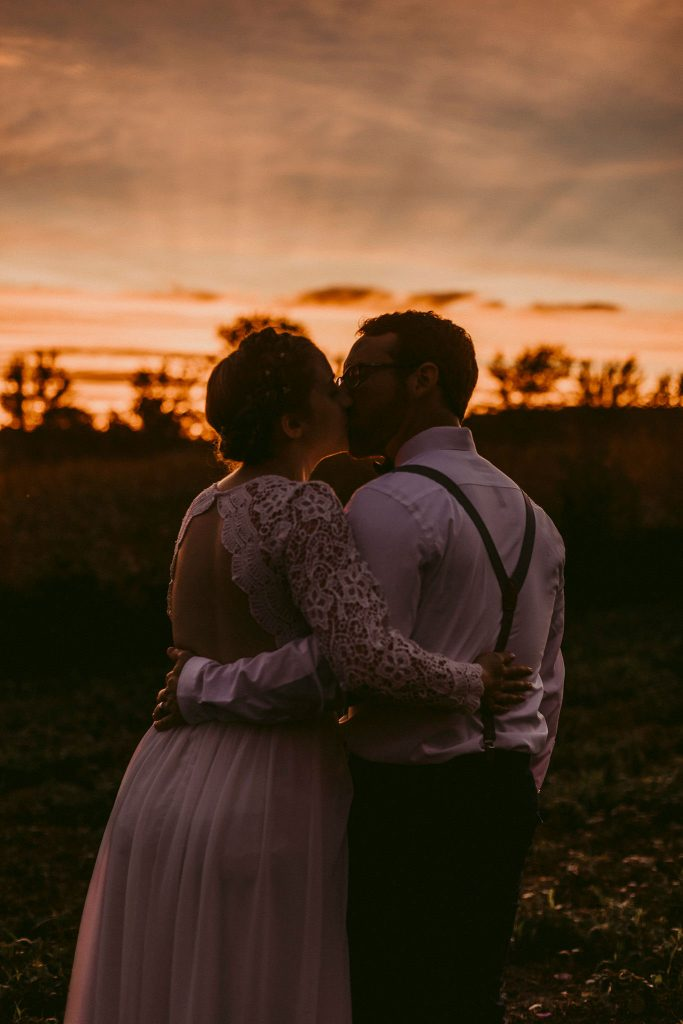 newlyweds kissing at sunset