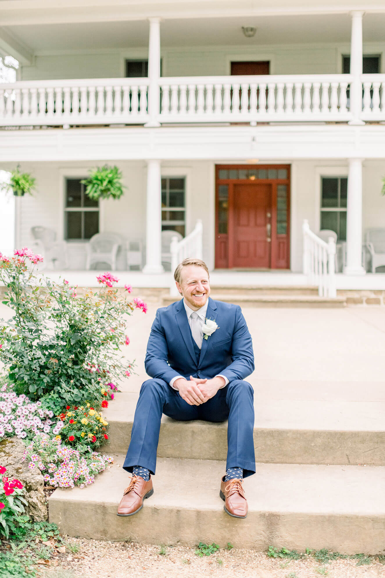 groom sitting on steps at sugarland barn