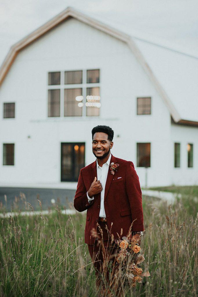 Groom in Burgundy Suit with Northern Haus wedding venue in background