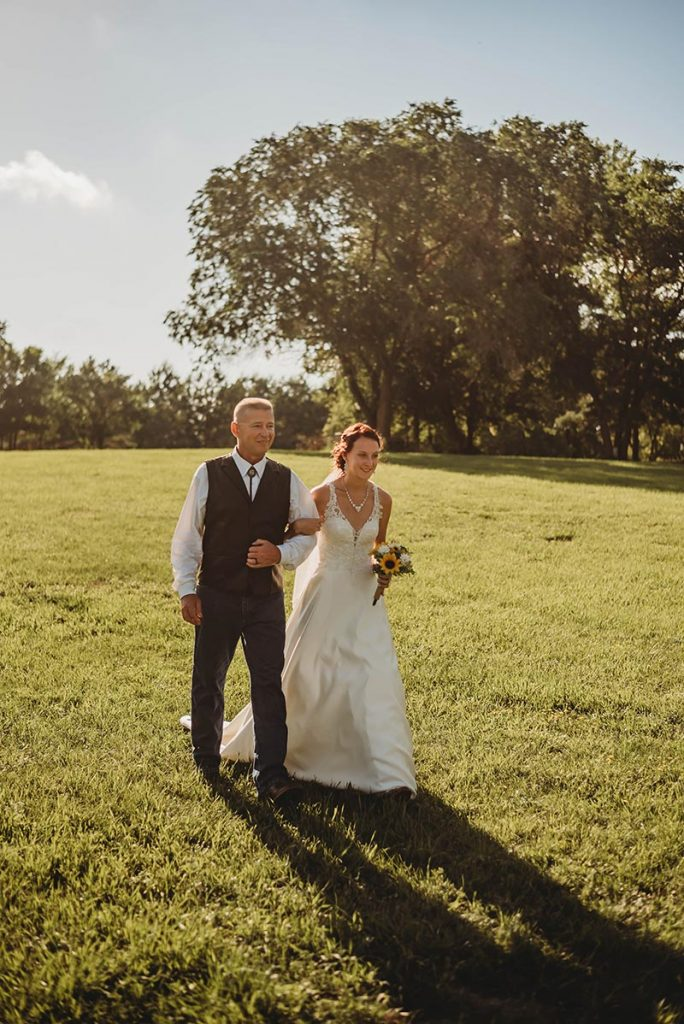 Bride Walking To The Alter in A Grassy Field